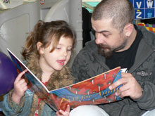 Photo of a man reading to a girl