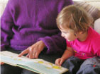 Child reading with grandparent